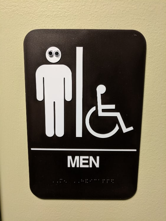 Googly eyes on bathroom sign