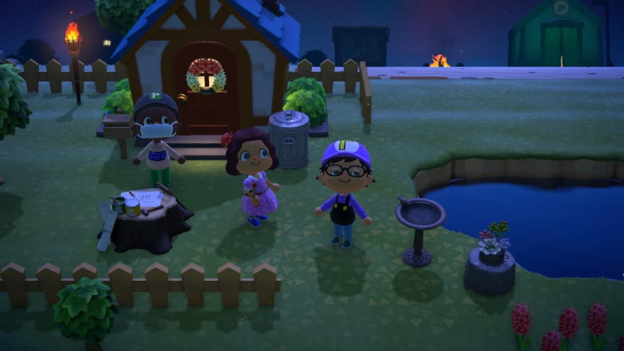 3 player characters from Animal Crossing stand near a house in the game