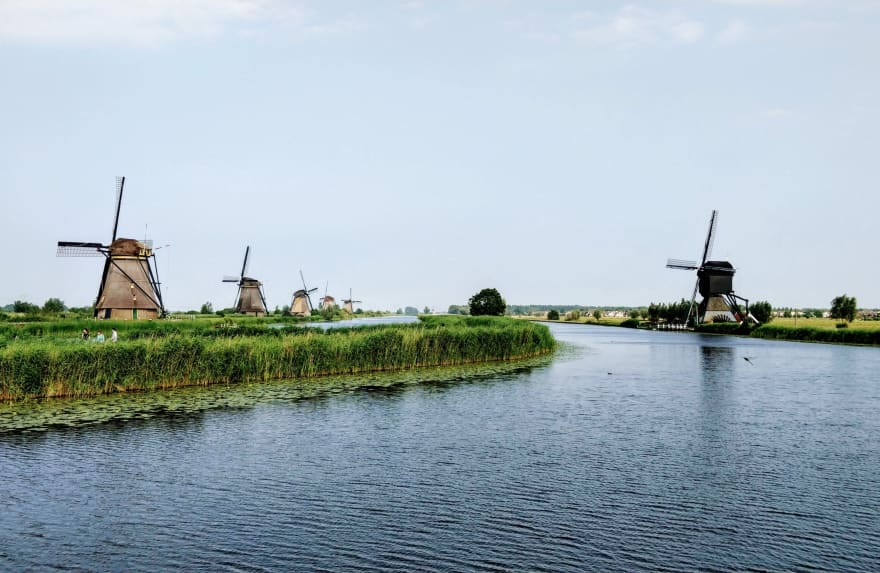"Photo called ""It's Own Kind of Tranquility"", displaying a series of windmills on either side of a 'water street (canal)' in Alblasserdam, The Netherlands"