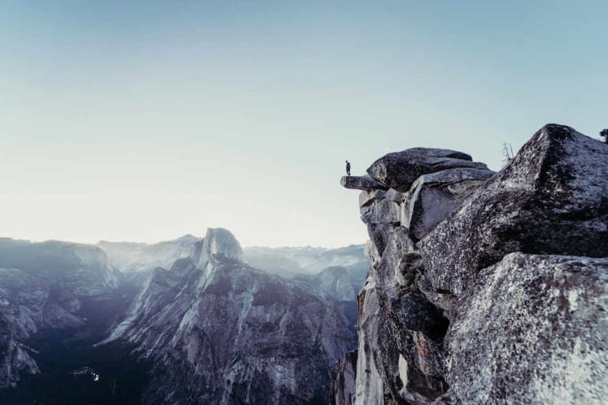 Person standing on a rock protruding from a cliff