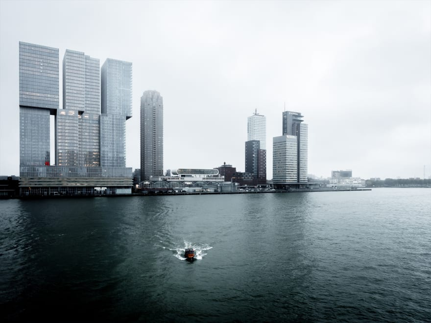 "Photo of ""De Rotterdam"", Rotterdam, Netherlands, with the building, the Cruise Terminal, and a small boat coasting towards the photographer on a gloomy day."
