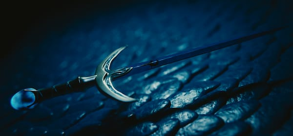 a sword in the dark hovering over a scaly surface below