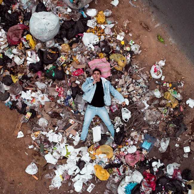 Man making the shush gesture with his finger over his lip, laying on a mound of trash. Photo by Jordan Beltran