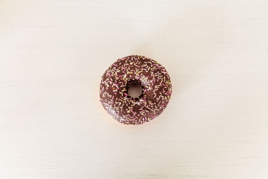 A chocolate covered donut with sprinkles