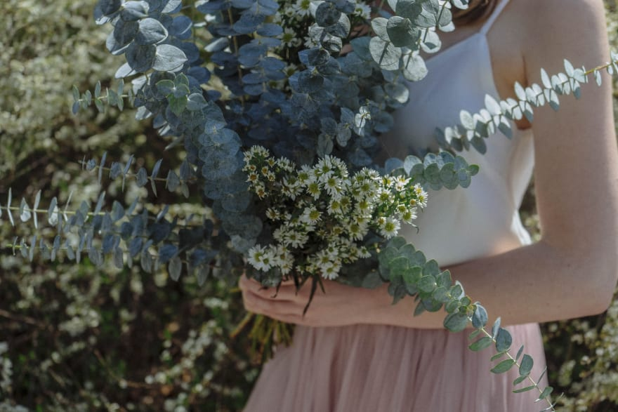 A bride holds a lovely green and white bouquet of flowers.