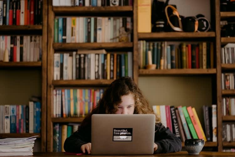 Pessoa sentada na frente do notebook estudando concentrada
