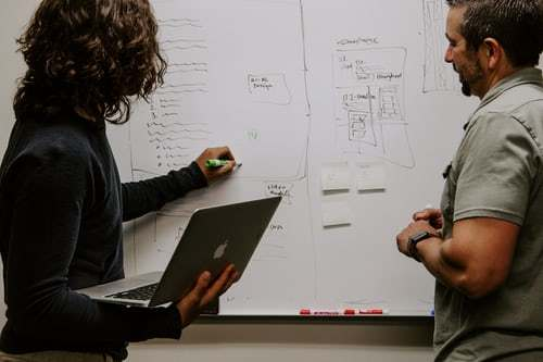 A woman and man taking notes on whiteboard