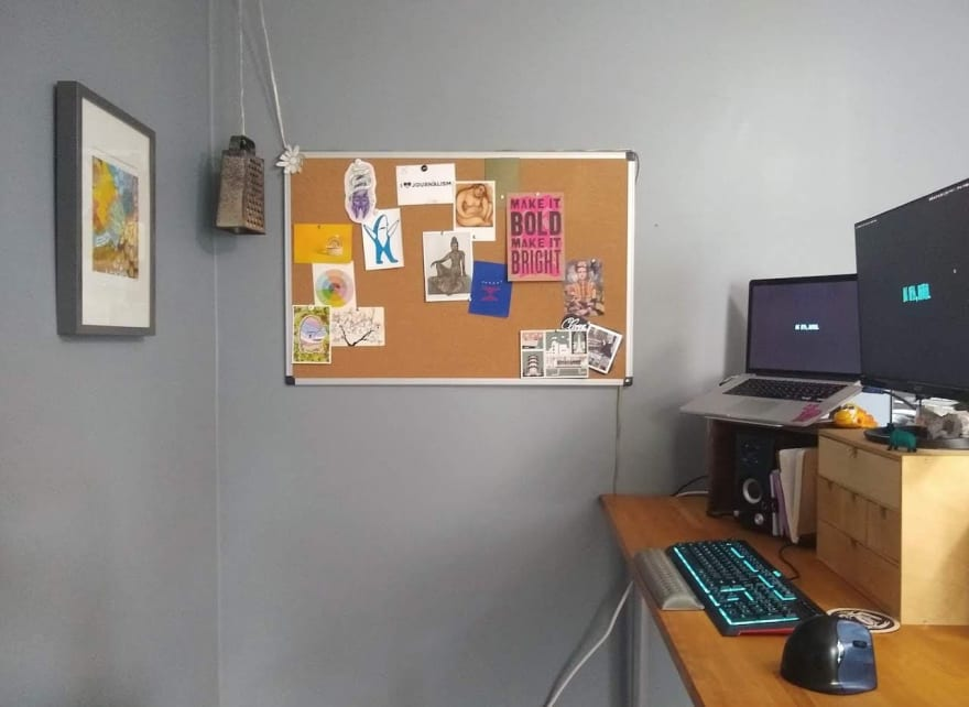 My standing desk with its accoutrements: a MacBook and peripherals, like an external monitor, keyboard, vertical mouse and speakers. The walls are painted a soothing blue grey and are decorated with artwork and a corkboard, also covered in art and postcards.