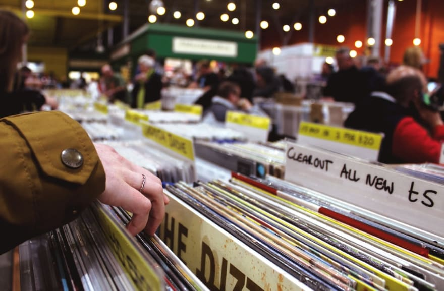Someone searching through a crate of vinyl records