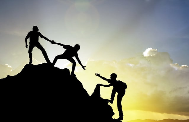 Three people reaching out to help each other climb up a mountain