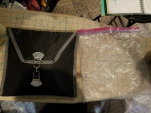 A black fabric envelope about the same size as a gallon ziploc bag of obvious age.