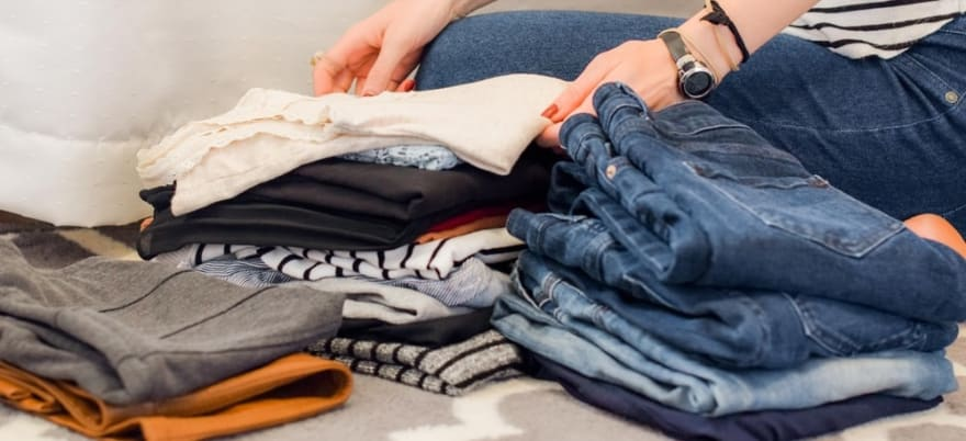 Stock photo of a person folding laundry and stacking it in piles by type