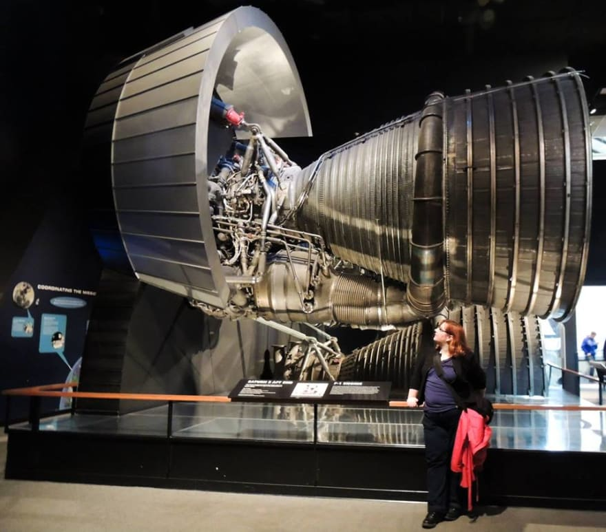 Image: Daniëlle, a woman with shoulder-length red hair, posing next to a cut-out of a Saturn V rocket engine.