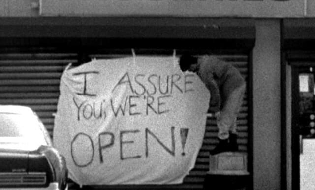 """A screenshot from the movie Clerks, in which Dante hangs the sign which reads """"I assure you we're open"""""""