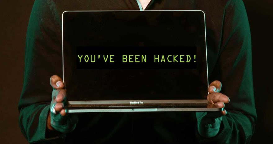 Someone holding a laptop with 'You've been hacked!' displayed upon the screen