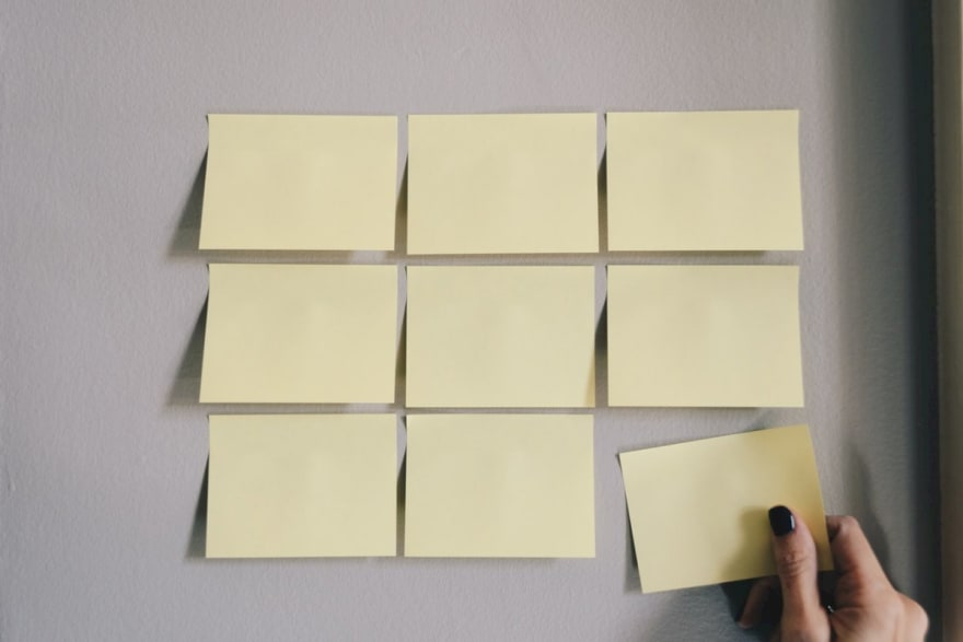 """Empty sticky notes on a wall"""