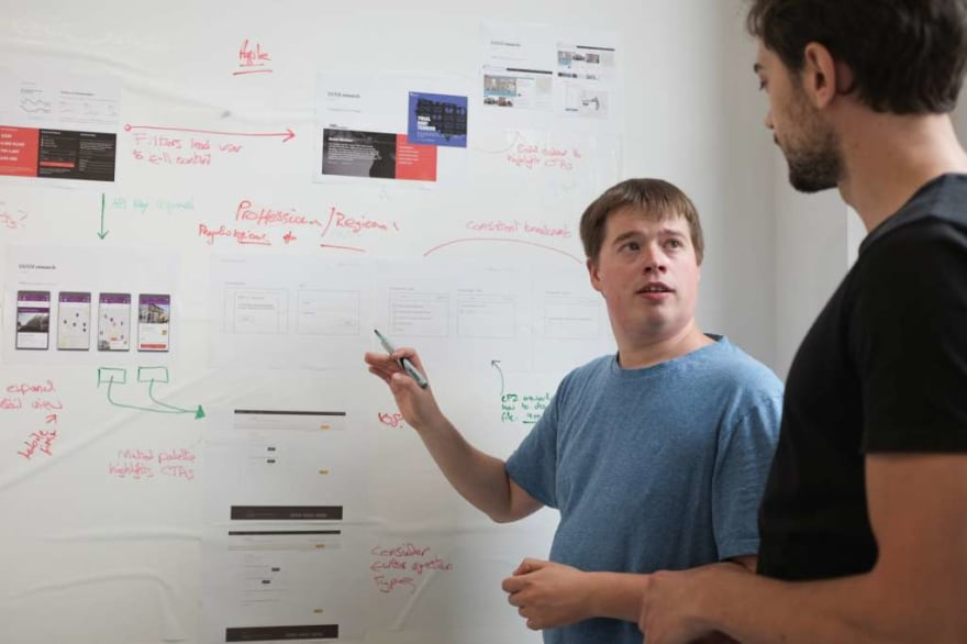 Two men stand in front of a white board and discuss a digital transformation project