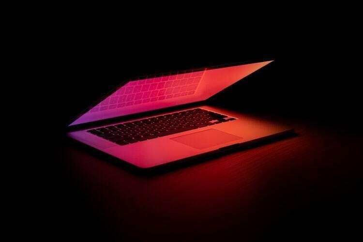 Notebook entreaberto com tela vermelha