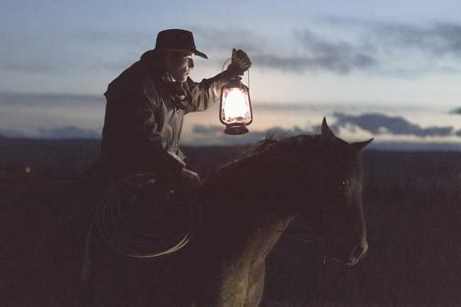 Man riding a horse, lighting his path with a lanterm by Priscilla De Preez