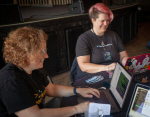 Two smiling white women, one with blond hair and one with pink hair, look at their computers together