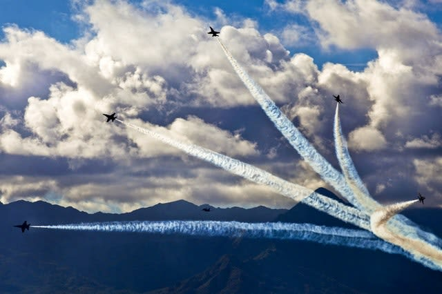 air show with 5 planes and smoke flying in different directions with mountains in background