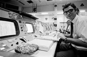 Black and white photo of John Aaron sitting at his desk in Mission Control.