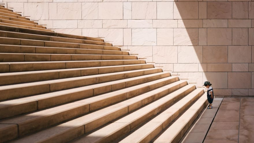 Image that symbolizes the beginning of her career, a little kid in front of a bunch of stairs