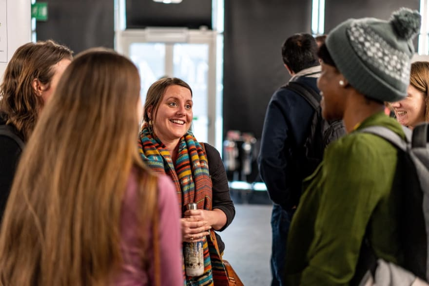 Five people talking in a group and smiling during one of the networking breaks