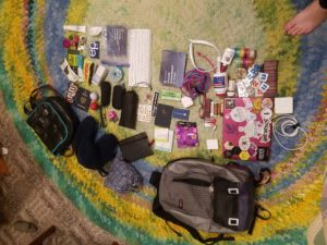 An array of bags and the things they contained, including laptop, cords, stickers, portable keyboard, medicine, neck pillow.