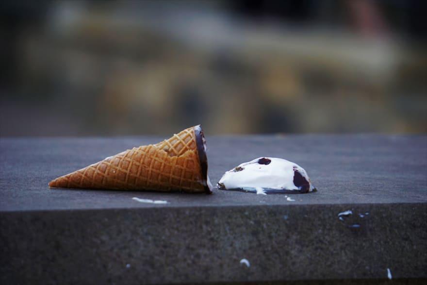 Melting ice cream cone spilled on sidewalk