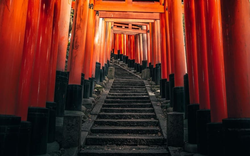 Picture of a set of stairs leading up through a series of Japanese gates