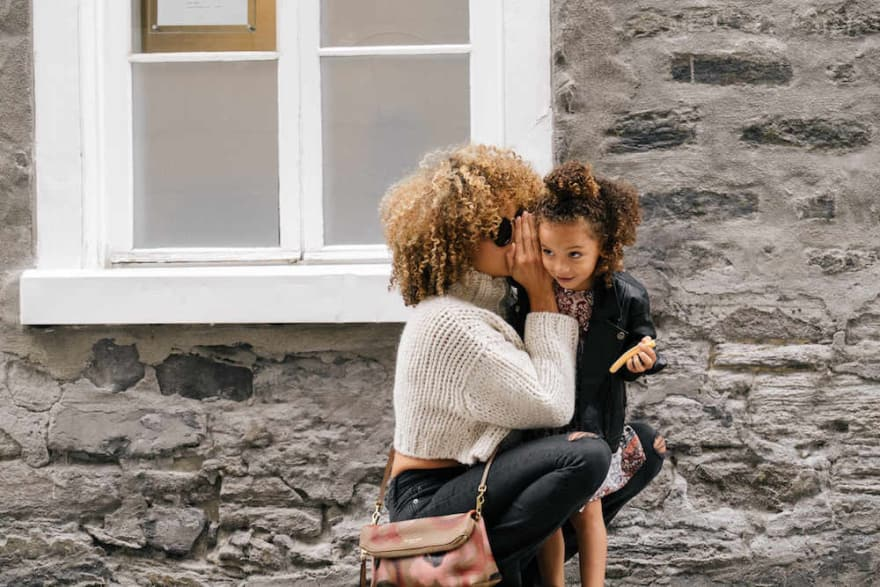 Woman whispering to her daughter