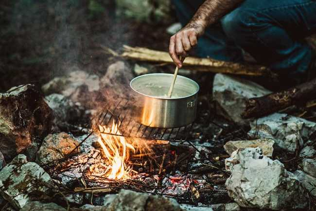 Photo of a man stirring a campfire cooking pot by Gary Sandoz