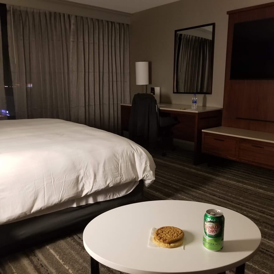 A hotel room at night. On the table are two cookies and a can of ginger ale
