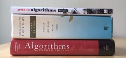 three books on algorithms stacked on top of each other sitting on a table being viewed from the side