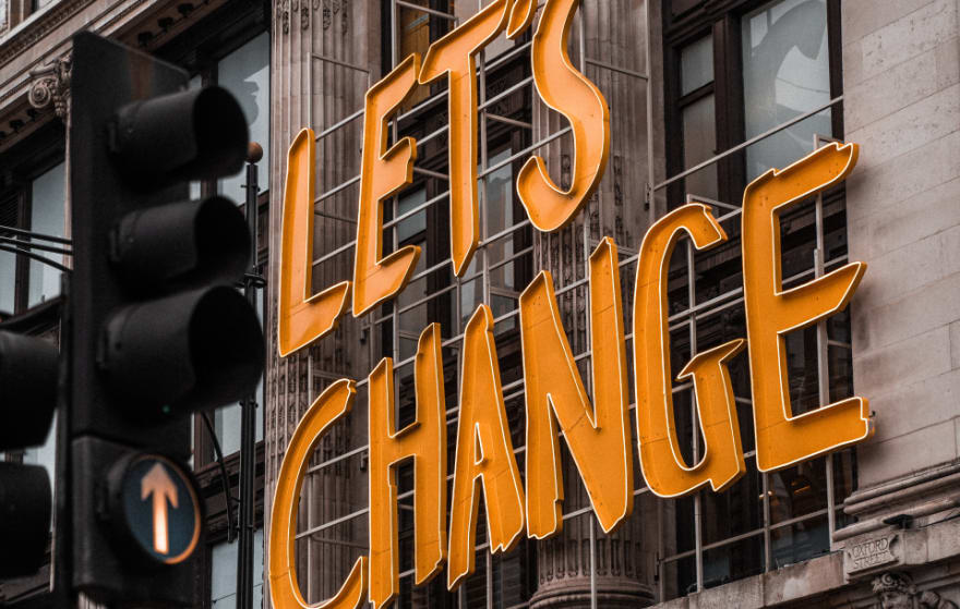 """A sign above a storefront that says """"Let's Change"""""""