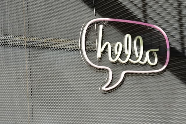 Neon sign on wall that reads 'hello'