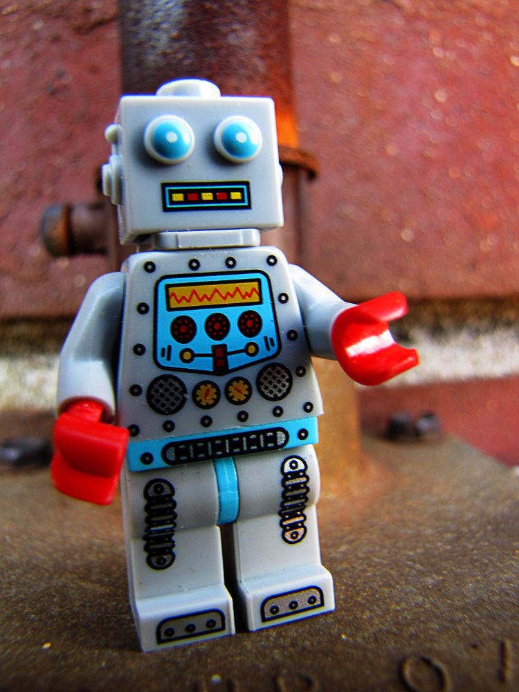 """""""A gray robot with a square head. he is standing in front of a brick wall."""""""