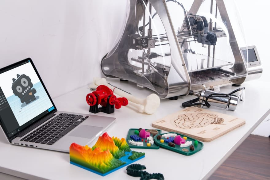 Laptop, 3d printer and a number of 3d printed colourful models on a desk
