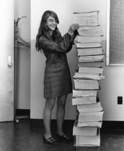 Margaret, in 1969, standing beside the listings of the actual Apollo Guidance Computer source code. Photo courtesy of the MIT Museum.