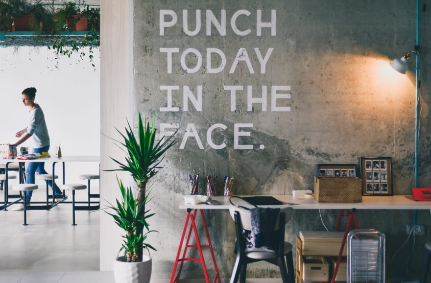Concrete wall with mural that says: punch today in the face