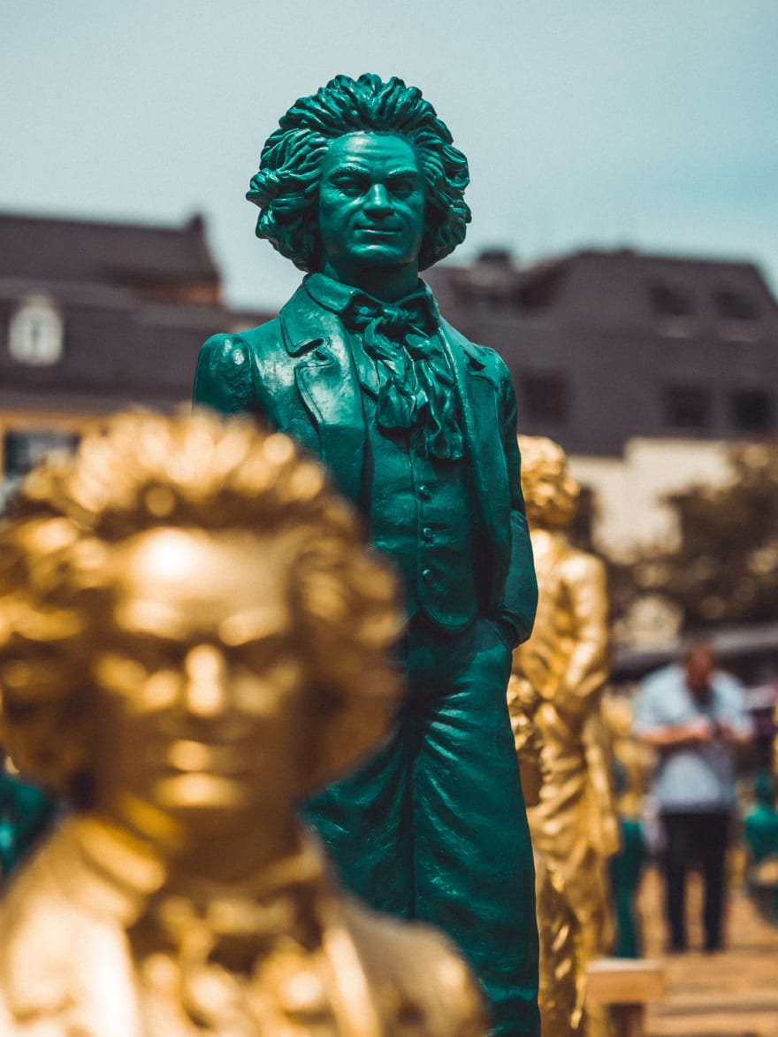 A large metallic statue of Ludwig van Beethoven with several smaller golden statues scattered around it. The large status is covered in a patina - a layer of green-ish oxidation that often forms on metals like copper and brass. The smaller statues are golden and out-of-focus.