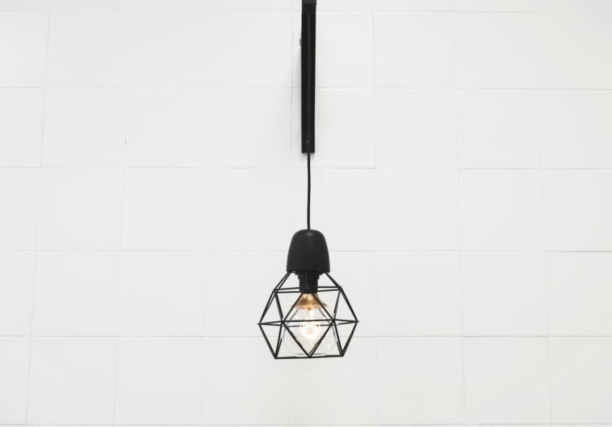 Minimalist photograph of a light bulb hanging from the ceiling.