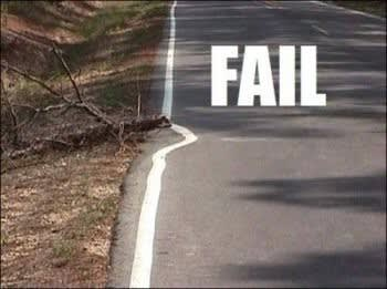 Road with the side line painted around a fallen tree branch, with the word FAIL in all caps