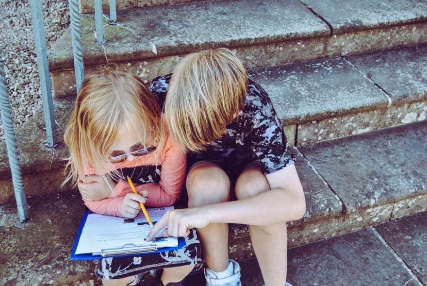 Image of two children sitting on a stoop. One of them is doing homework. The other is trying to help them with it.