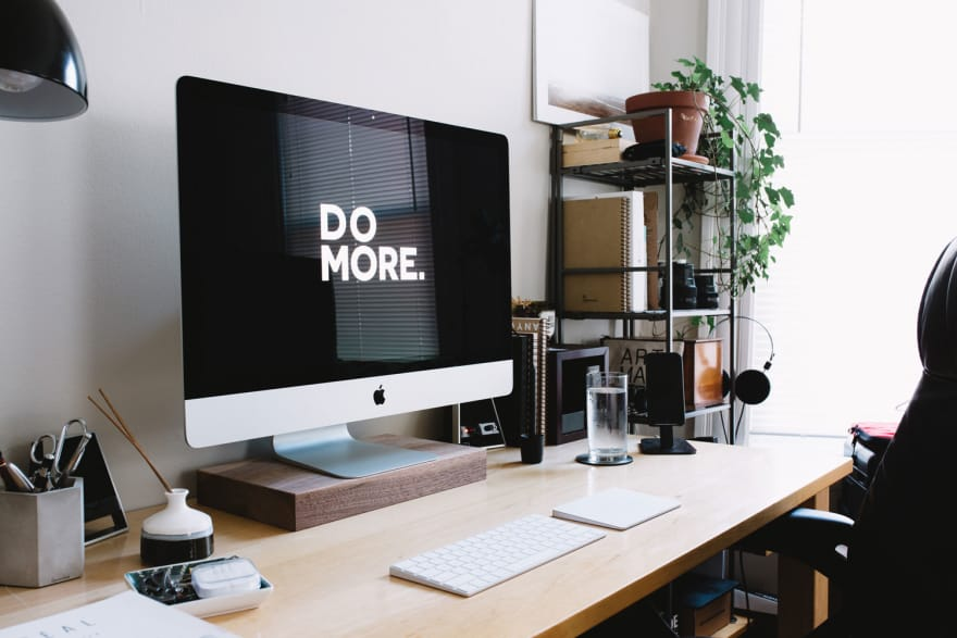 Tidy desktop setup with and iMAC that has a wallpaper prompting you to do more