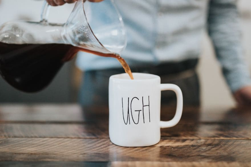 """Coffee mug labeled with """"ugh"""" being refilled with coffee."""