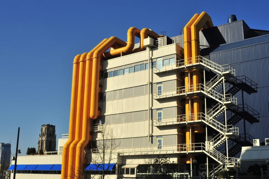 Photo of the Centrale Bibliotheek in Rotterdam, The Netherlands: an industrial looking building with metallic walls and various yellow pipes on the side.