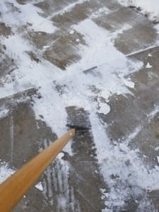 Wooden-handled tool with a hoe-shaped metal cutting edge, scraping compacted snow off a driveway