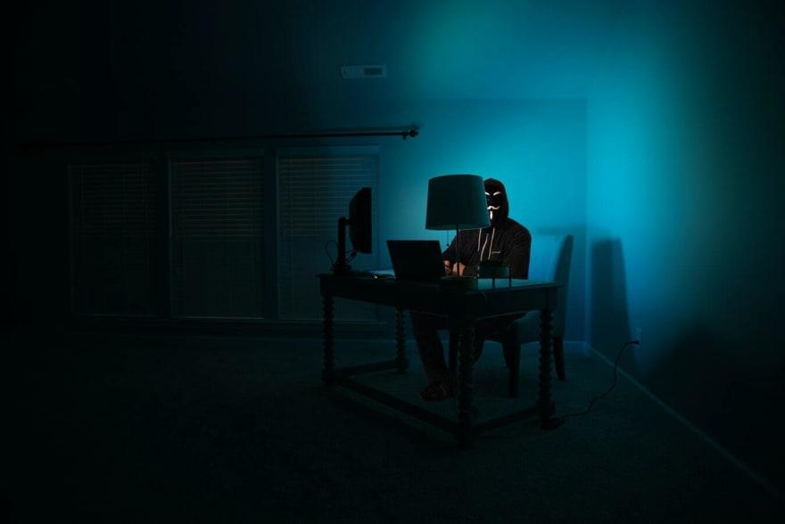 person in hoodie on computer in dark room